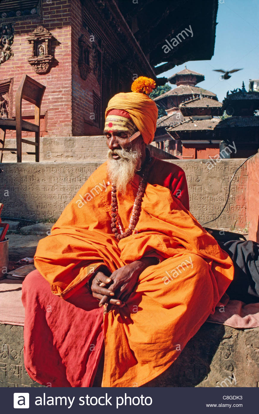 A Hindu ascetic or sadhu, sits on temple steps in Durbar Square. - Stock Image