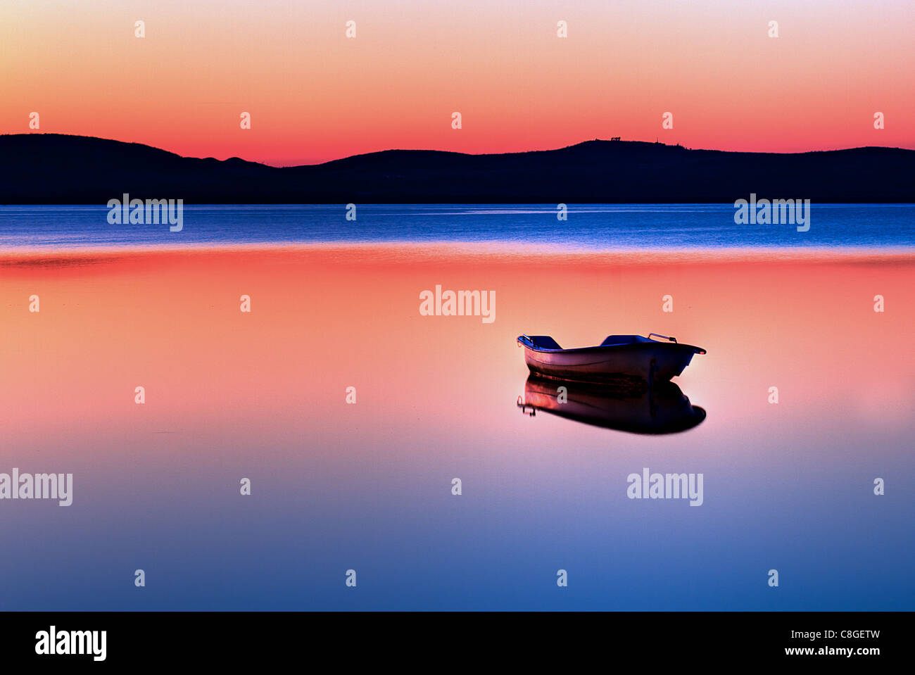 Scenic view of small fishing boat in calm water at sunset with hills in the background. - Stock Image
