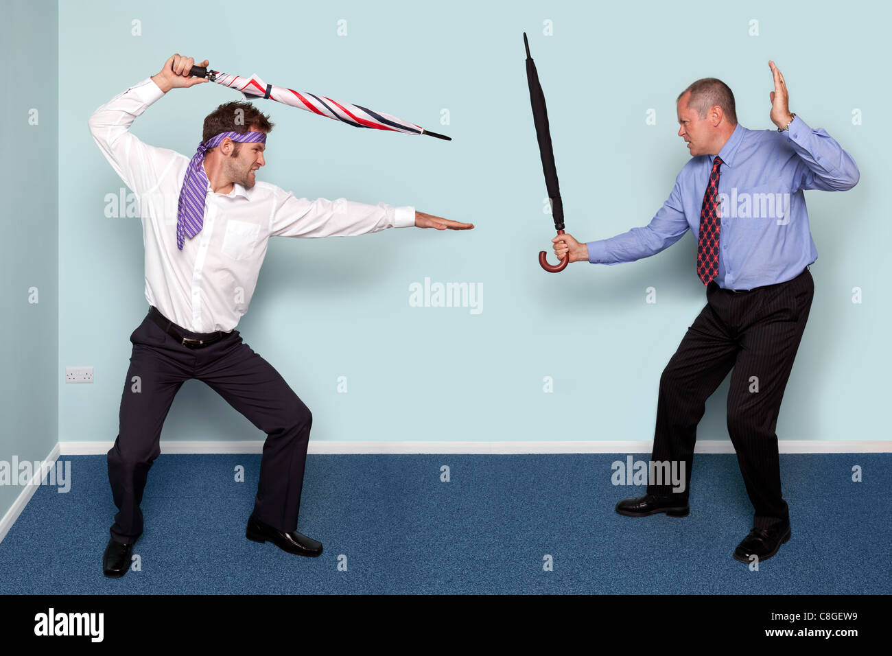 Photo of two businessmen having a sword fight using umbrellas, good image to convey conflict, rivalry or disagreement. - Stock Image