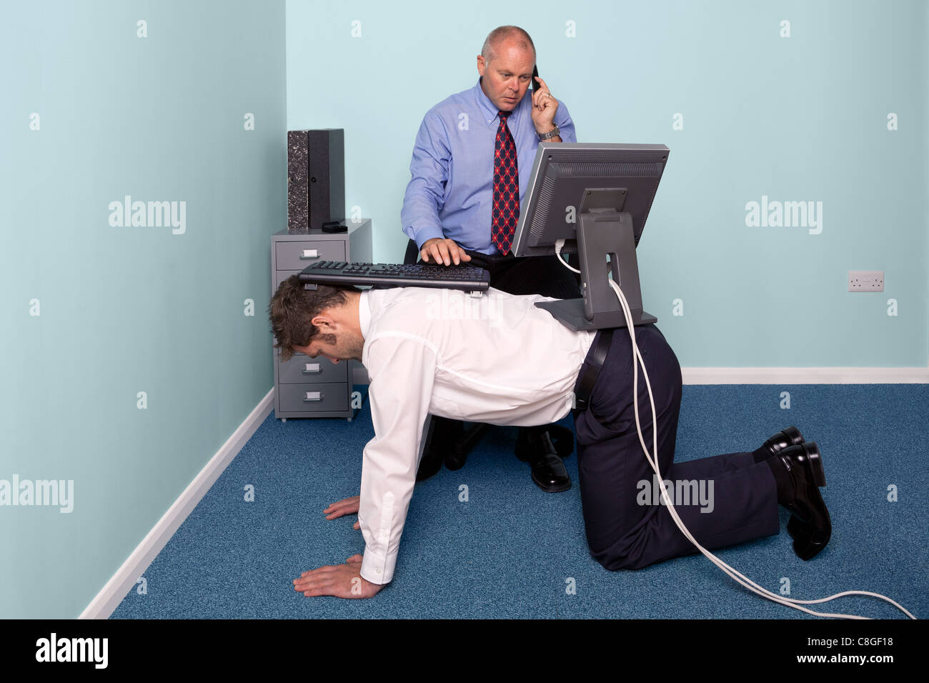Photo of a businessman using a work experience employee for his desk - Stock Image