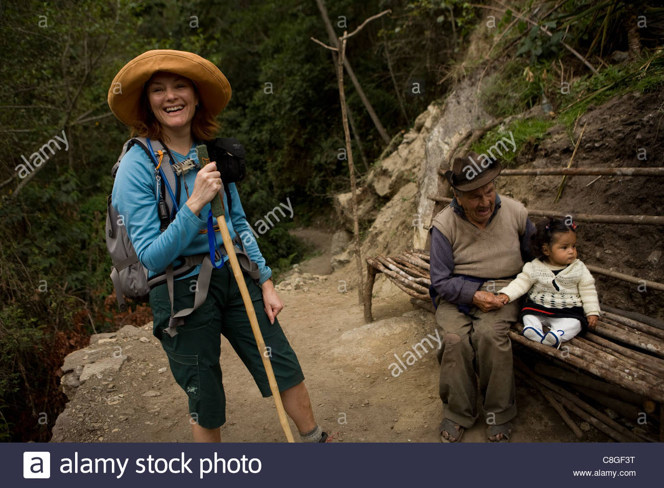 A hiker pauses to meet a 100 year old man and his great granddaughter. - Stock Image