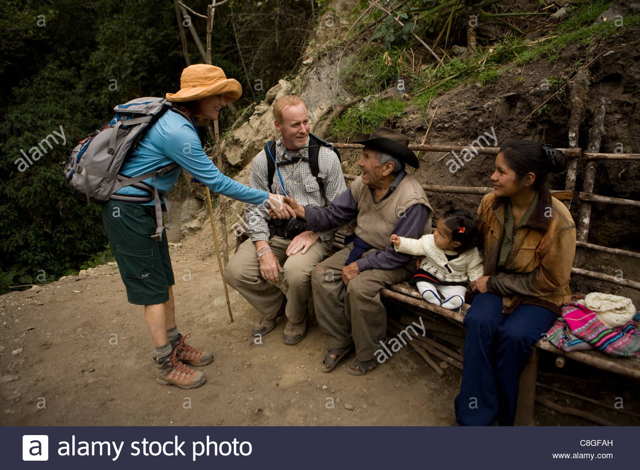 A hiker pauses to meet a 100 year old man and his family. - Stock Image
