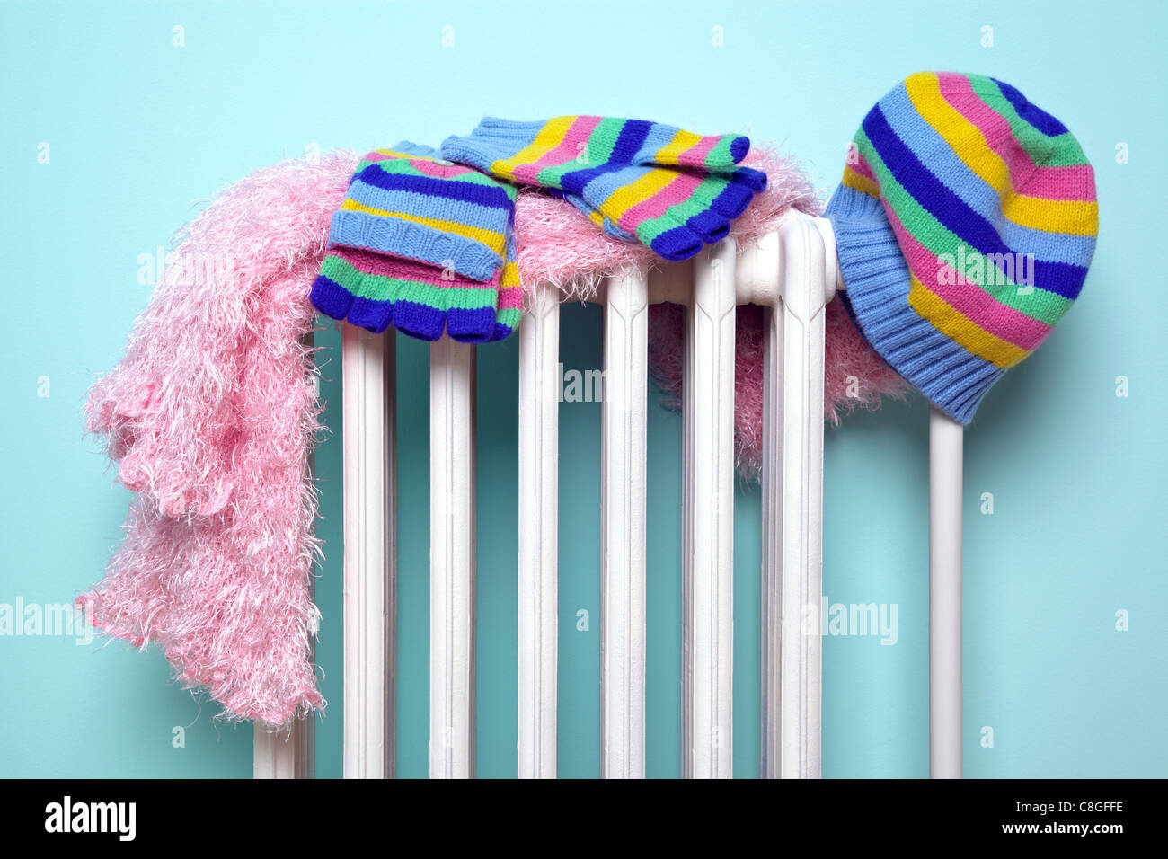 Photo of a girls hat, scarf and gloves drying on an old traditional cast iron radiator, good image for winter related - Stock Image