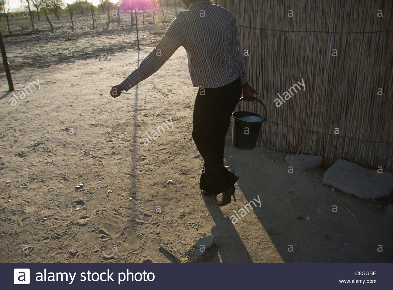 A woman fetching water for her one-room house. - Stock Image