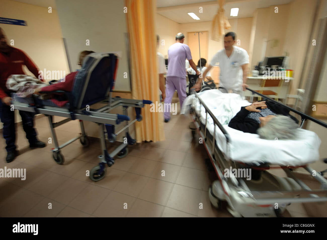 Motion blurred dynamic photo of healthcare professionals moving patients in gurneys in an hospital - Stock Image