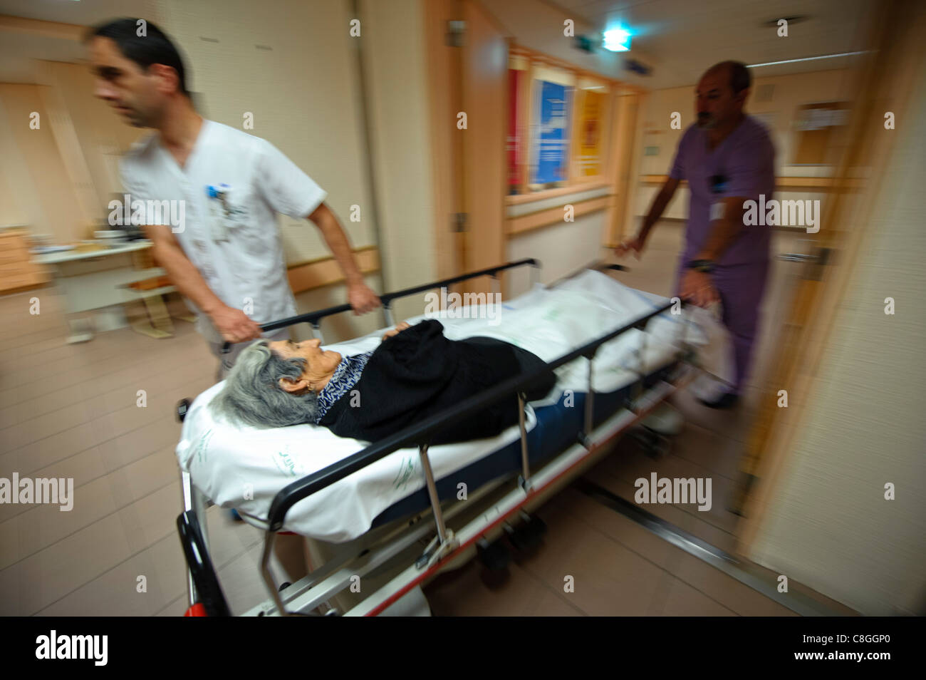 Motion blurred dynamic photo of healthcare professionals moving an old woman on a gurney in an hospital - Stock Image