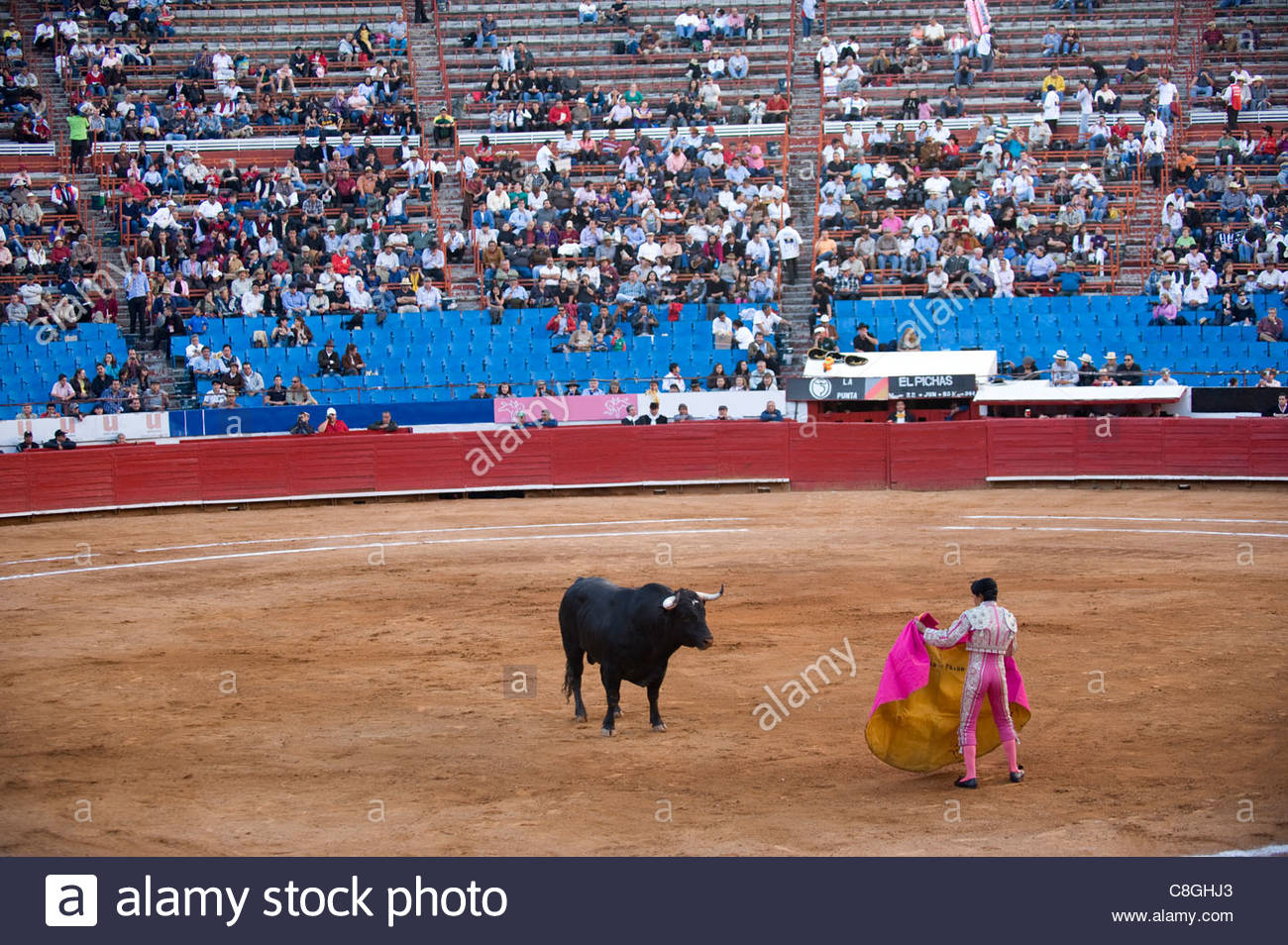 A bullfight in Mexico City, spectators watch the bull and Matador. - Stock Image