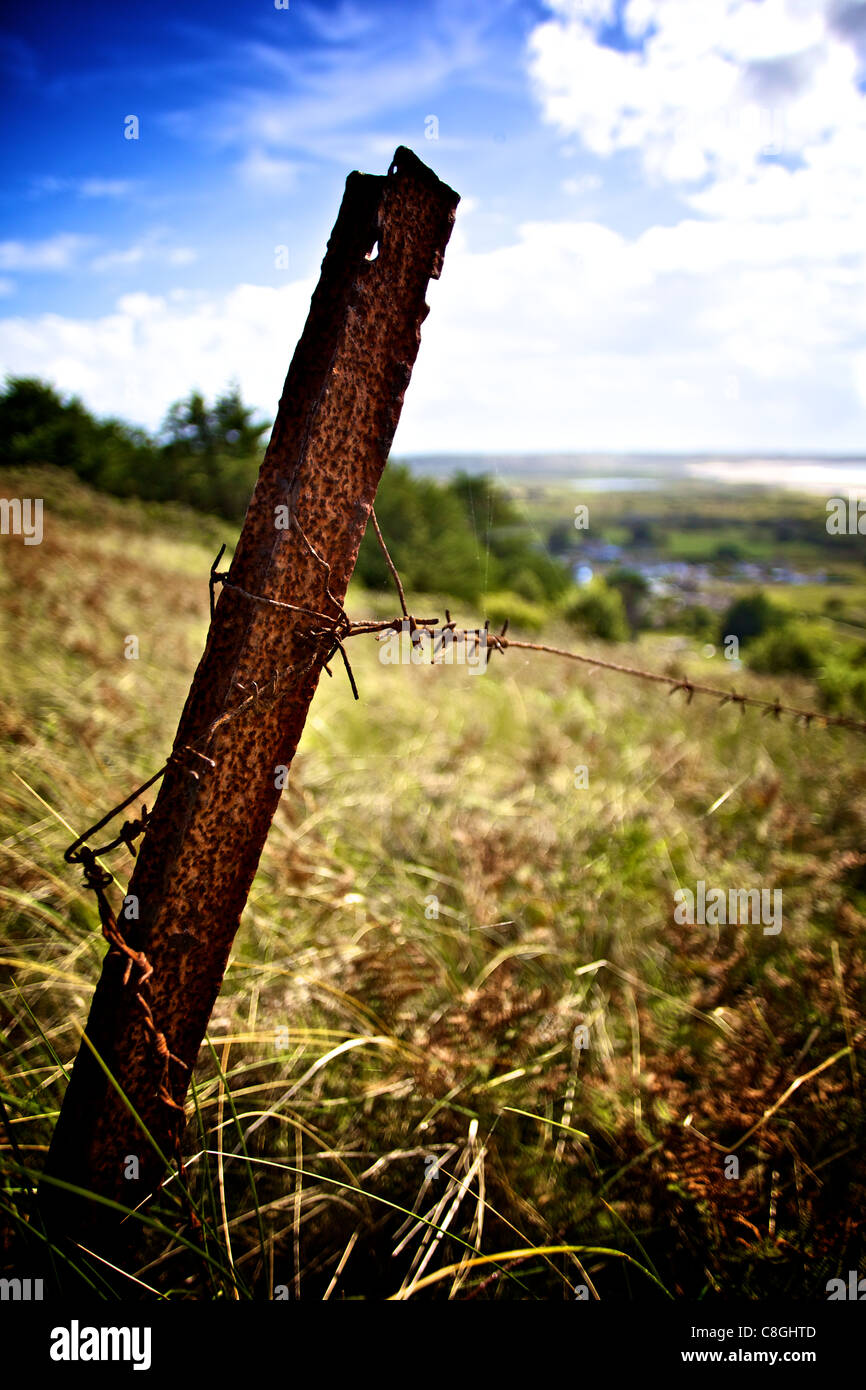 rusty iron fence post with barb wire attached in a field overlooking the beach at st ouen's bay jersey - Stock Image