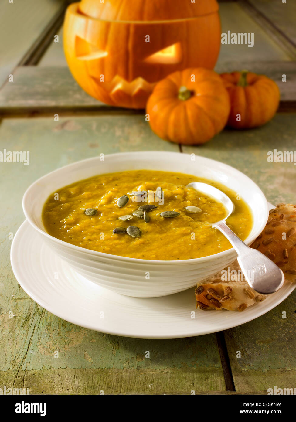 Pumpkin & Bacon Soup with a traditional Haloween pumpkin with a carved face Stock Photo