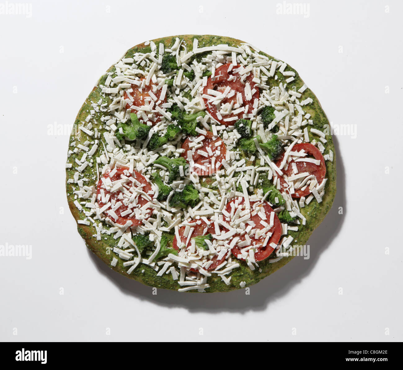 Looking downwards on a frozen pizza. Broccoli, pepperoni, cheese and pesto sauce - Stock Image