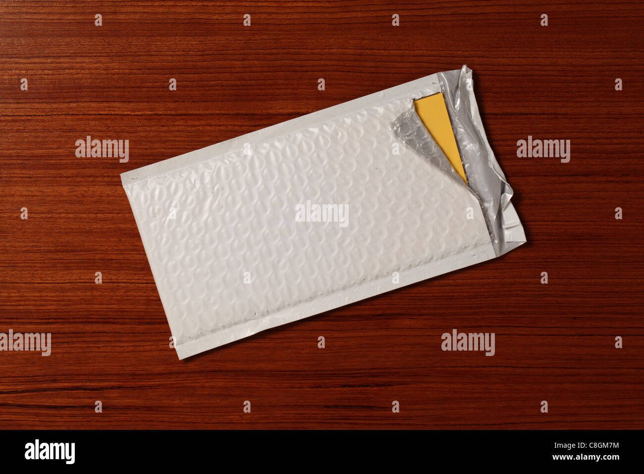A white padded mailing postal envelope slightly torn open on the end exposing a yellow document. Wooden desk surface. - Stock Image