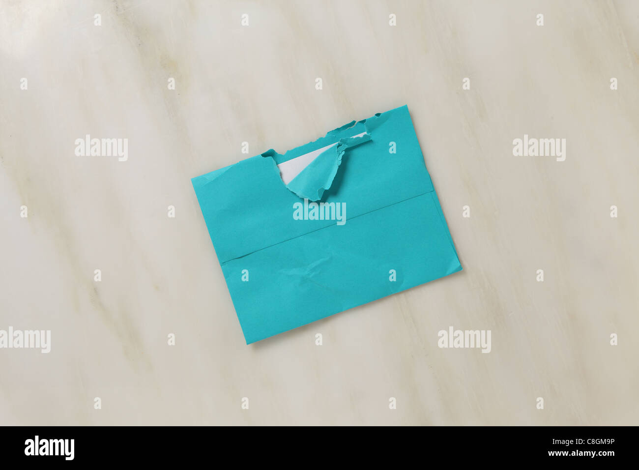 A used and slightly torn open postal envelope on a marble surface Bright teal blue colored envelope - Stock Image