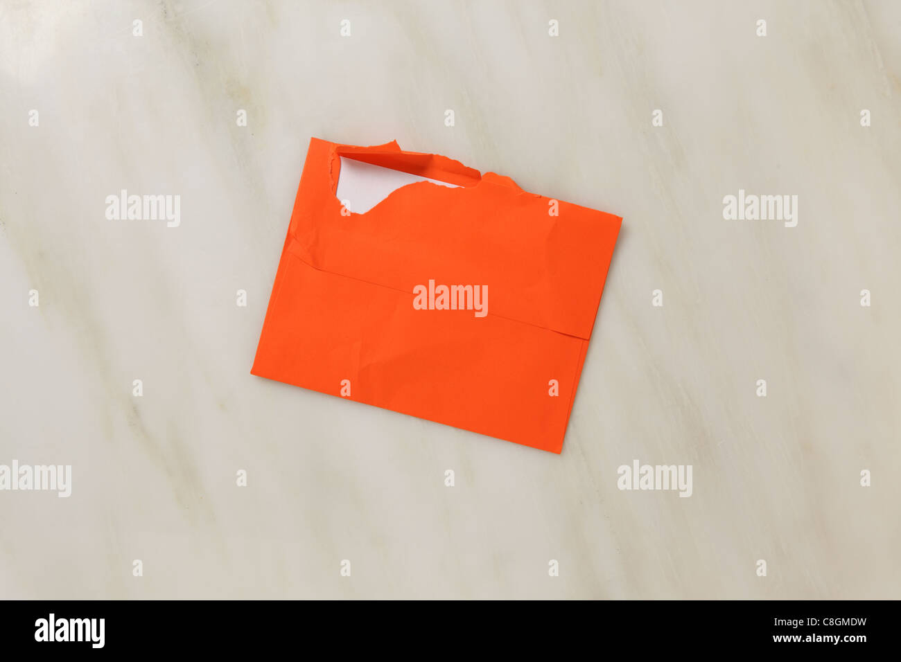 A used and slightly torn open postal envelope on a marble surface. Bright orange colored envelope - Stock Image