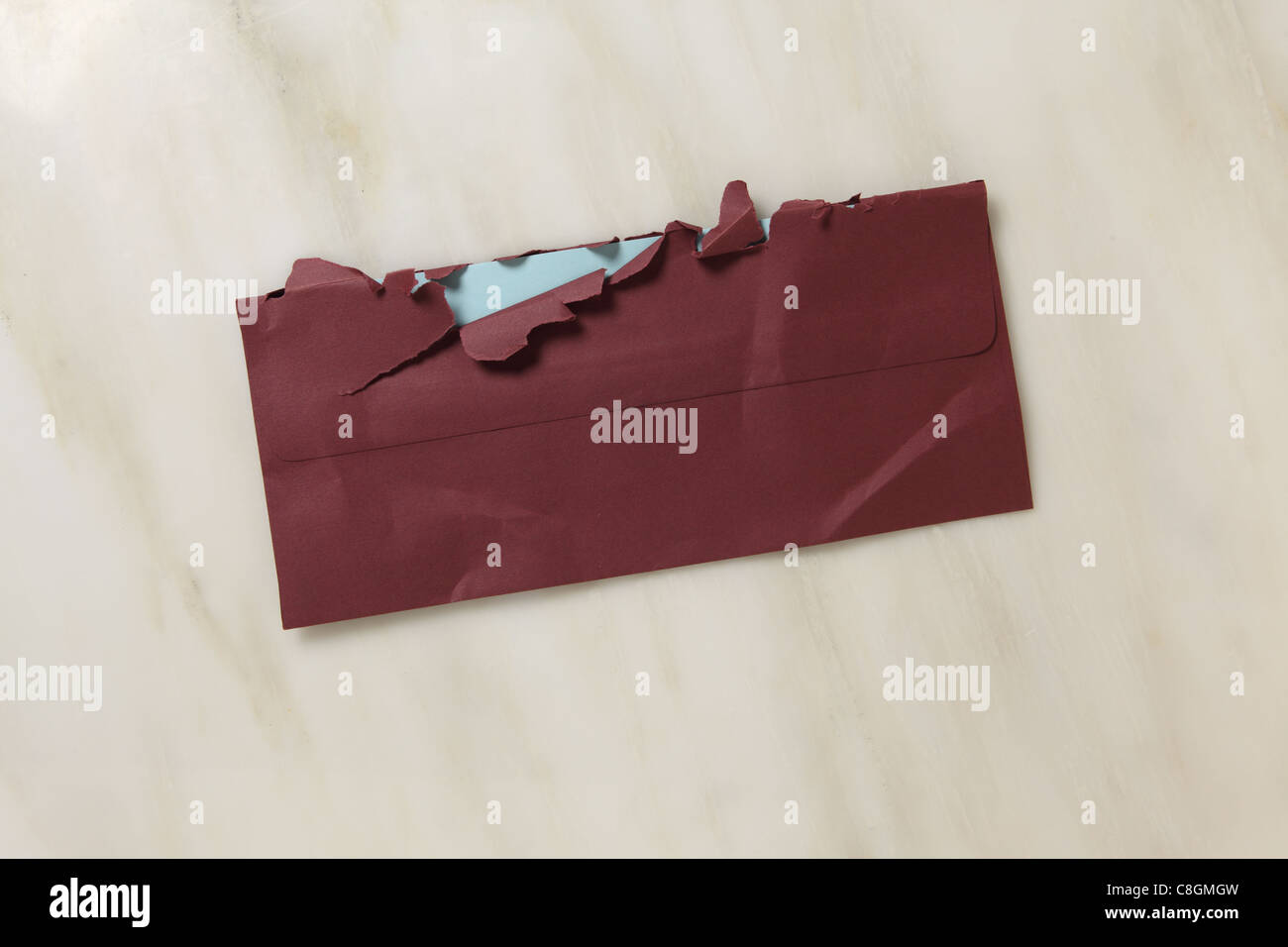 A used and slightly torn open burgundy postal envelope on a marble surface - Stock Image