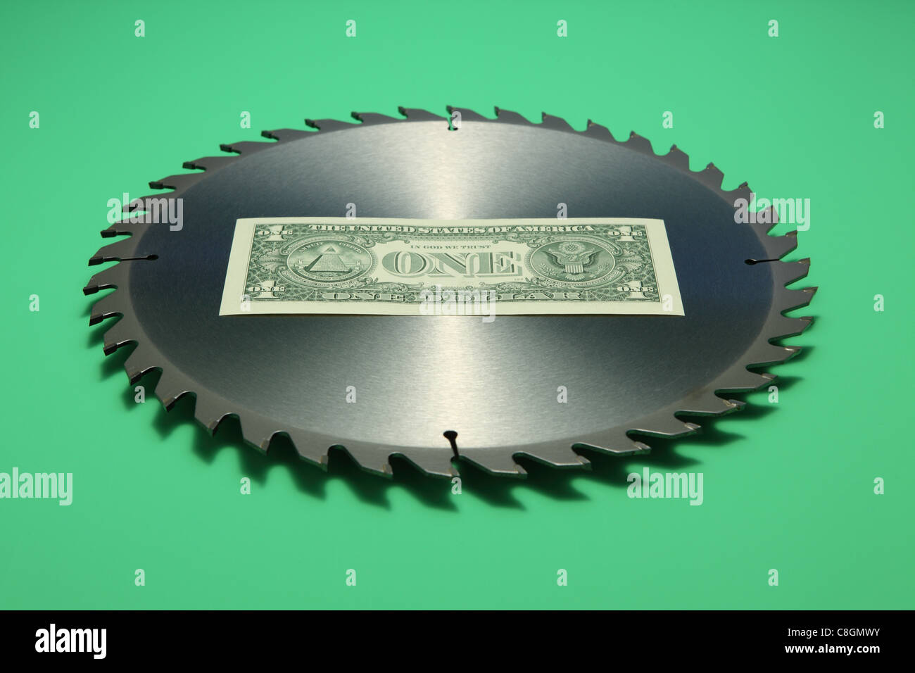 One US dollar banknote in the middle of a metal circular saw blade. Bright green background, banknote back facing - Stock Image