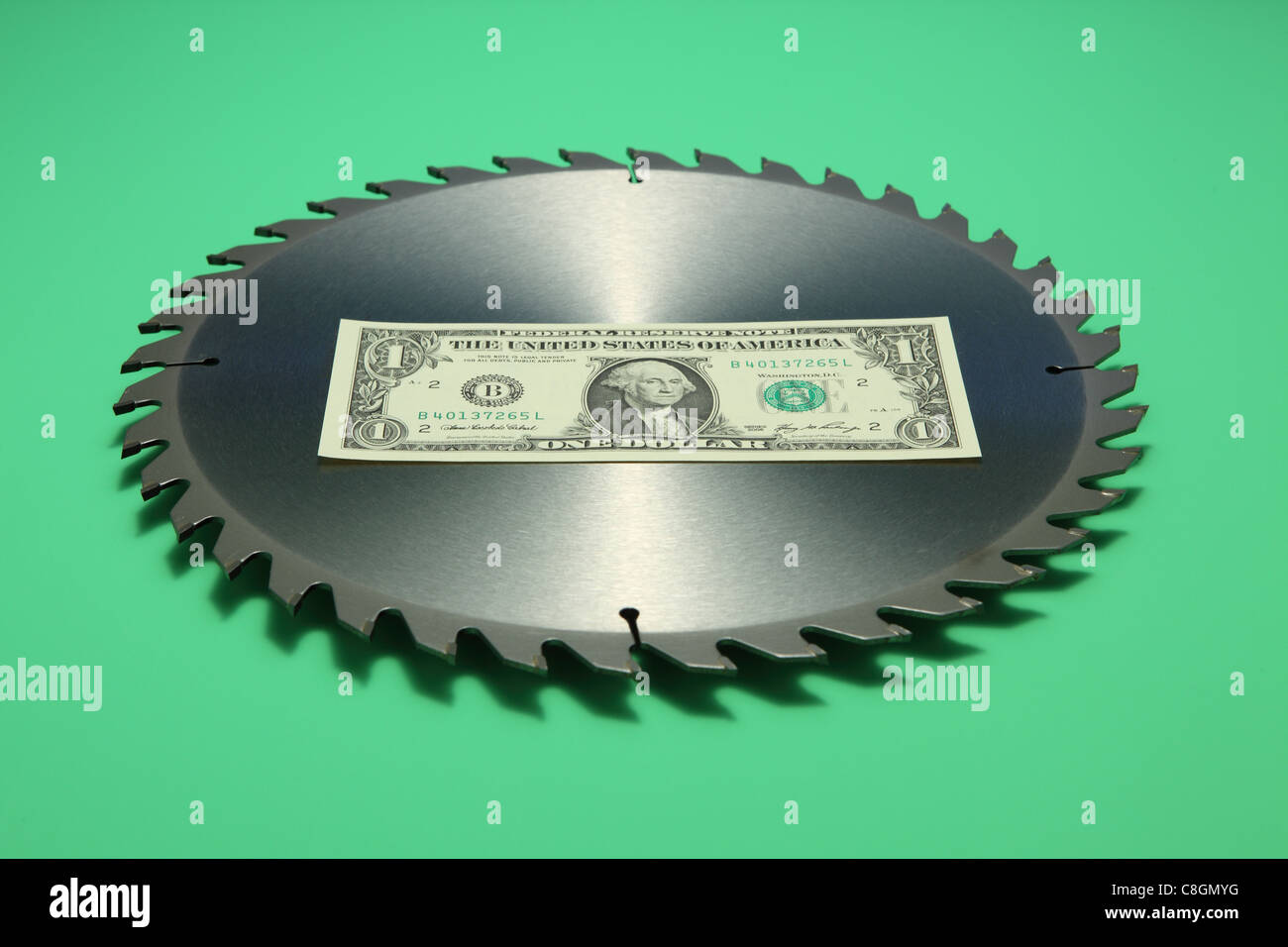 One US dollar banknote in the middle of a metal circular saw blade. Bright green background, banknote front facing - Stock Image