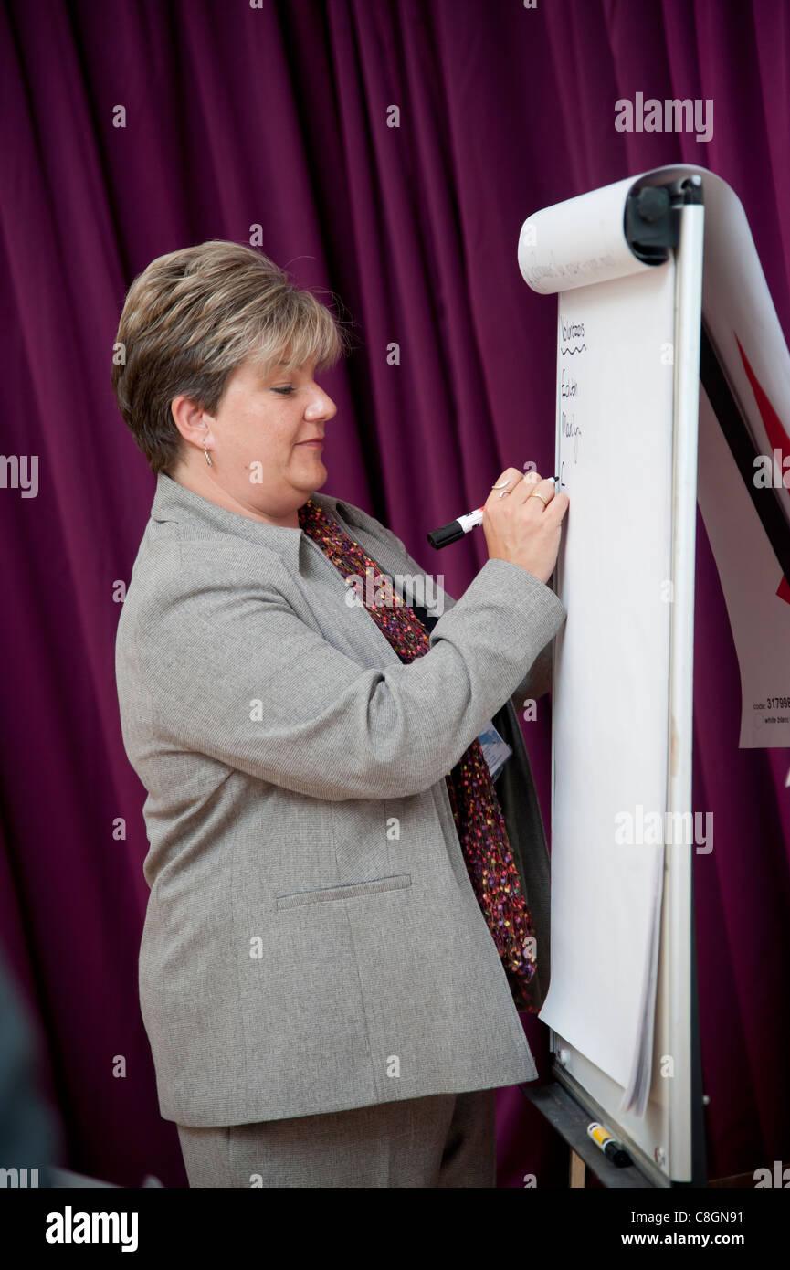 A business woman writing notes on a flip chart at a meeting presentation seminar, UK - Stock Image