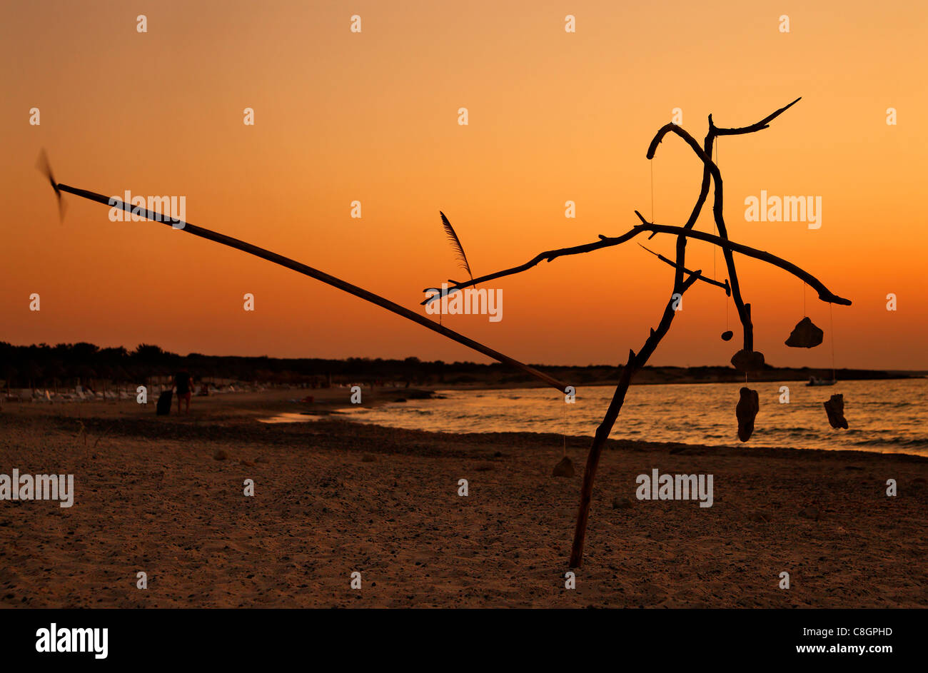 """Sunset photo from Chrissi island. In the foreground a strange """"sculpture"""" by unknown artist reminding Calder's mobiles. Stock Photo"""
