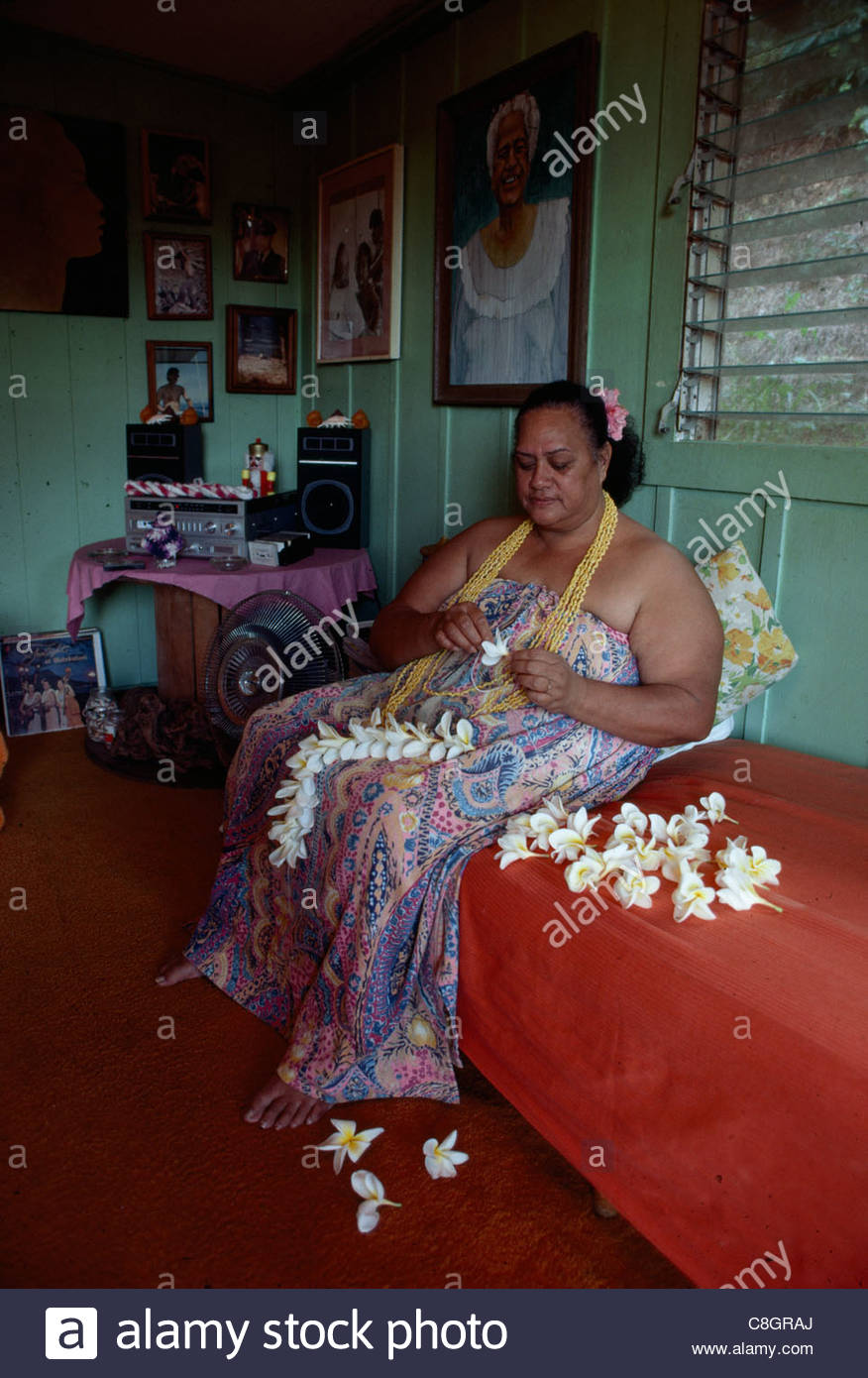 A  traditional Hawaiian woman making a flower lei by hand at home. - Stock Image