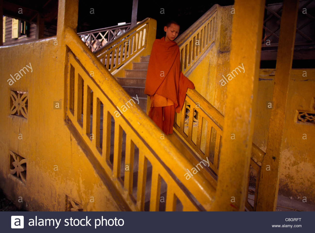 A monk walks down stairs at a temple in the city's center. - Stock Image