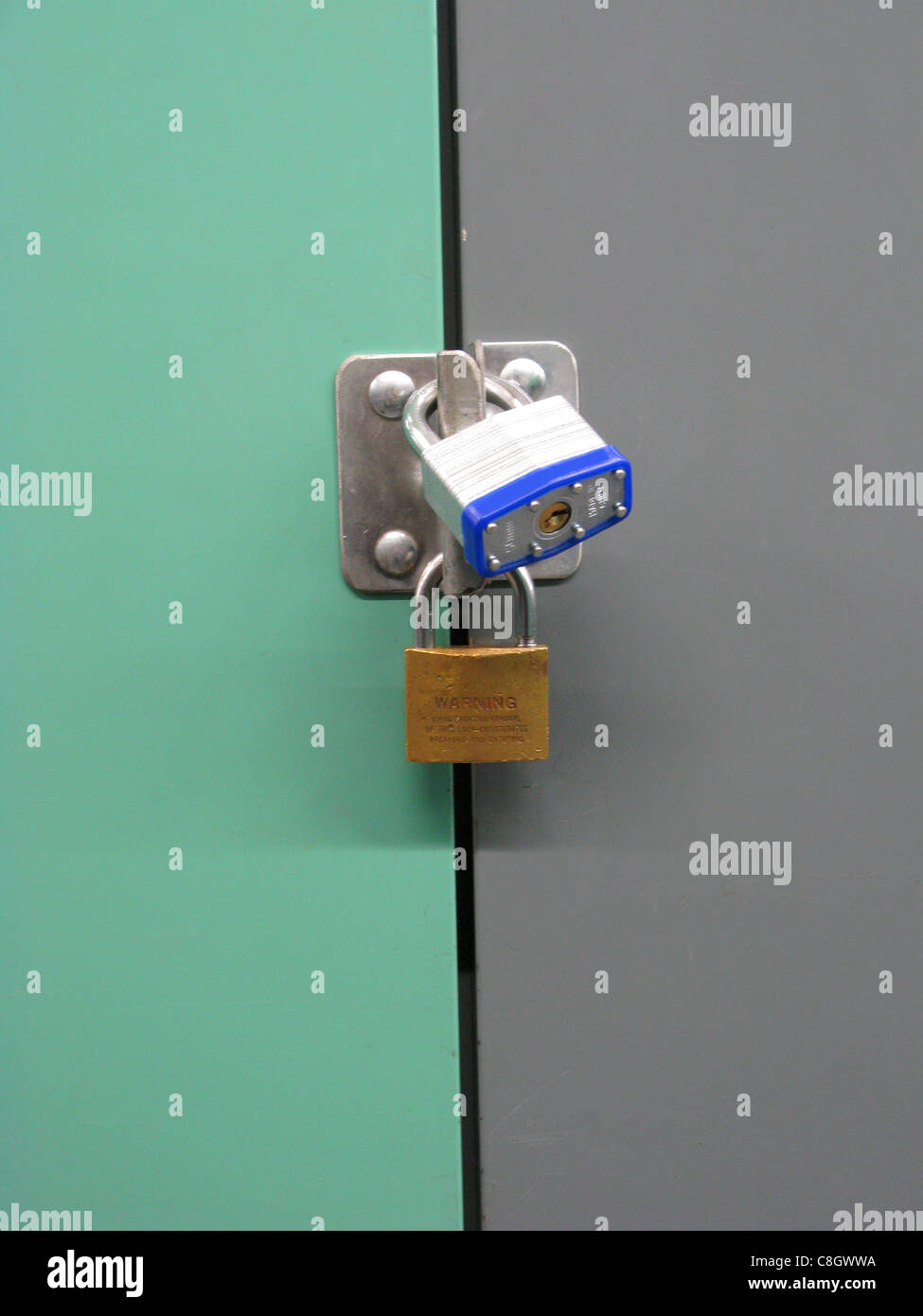 Two padlocks on a metal storage door door - Stock Image