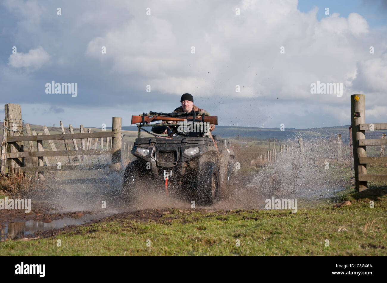 A man riding a quad bike (ATV) through a gate with water flying up from the wheels on an Autumn day, in Weardale - Stock Image
