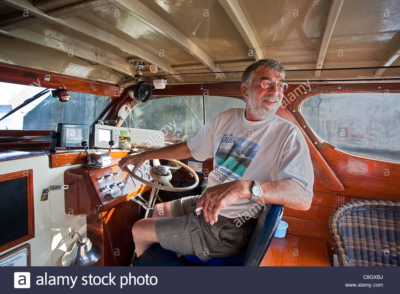 A fishing guide at the wheel of his antique fishing boat. - Stock Image