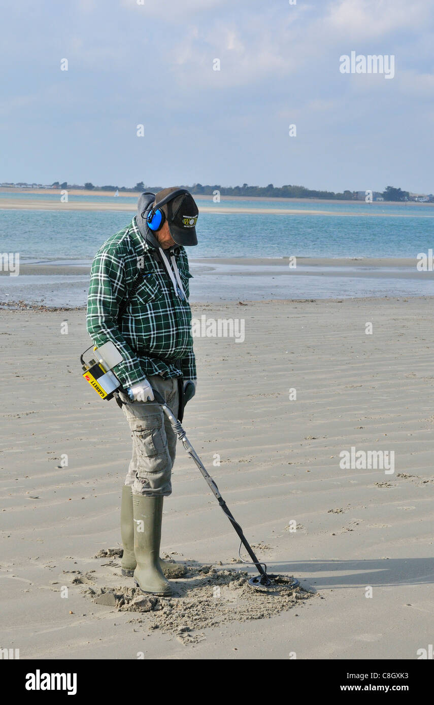Man with metal detector  looking for lost valuables  on West Wittering beach  after the weekends crowds had departed - Stock Image