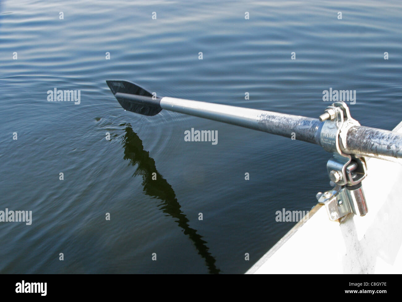 A oar of a row boat slightly above the water's surface - Stock Image