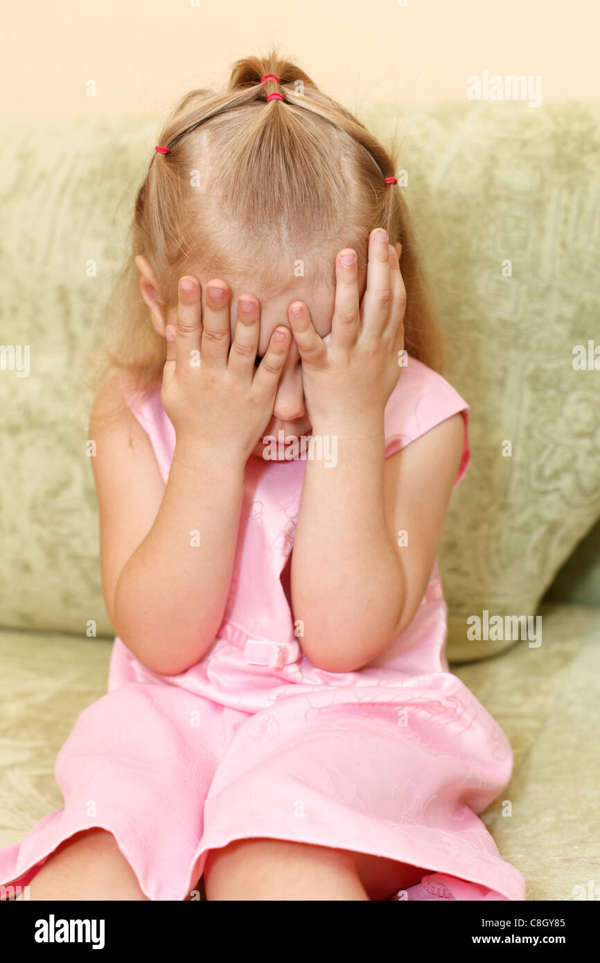 Little child a girl in pink dress sitting on sofa in domestic room and closes face by hands. One small Russian kid. - Stock Image