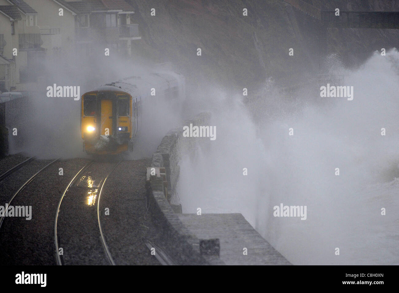 A train is battered by waves at Dawlish in Devon as storms hit the south west of England. - Stock Image