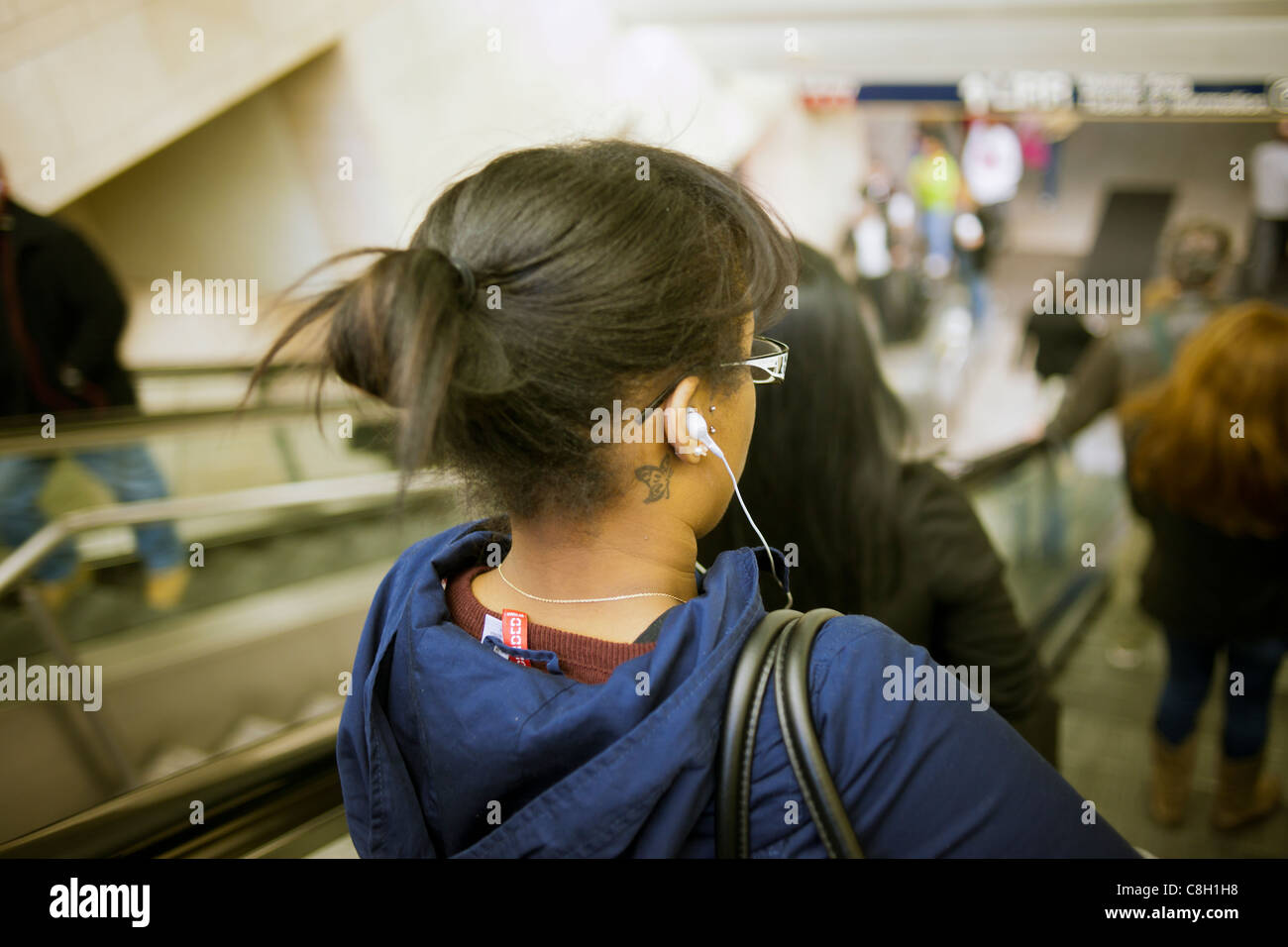A woman separates herself from the rest of the world listening to her iPod on the subway in New York - Stock Image
