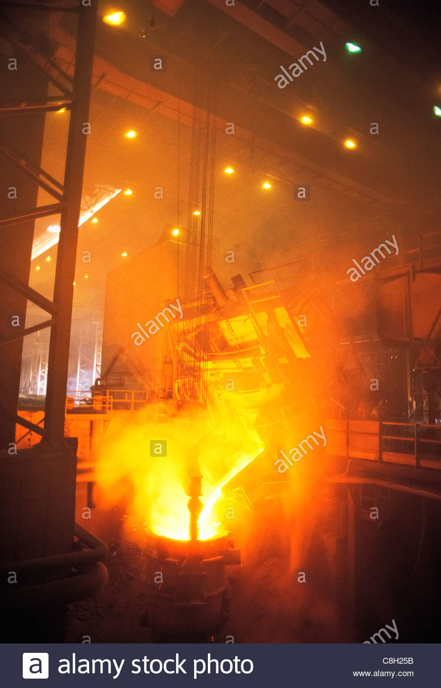 Molten metal pouring out of the blast furnace at a steel mill. Stock Photo