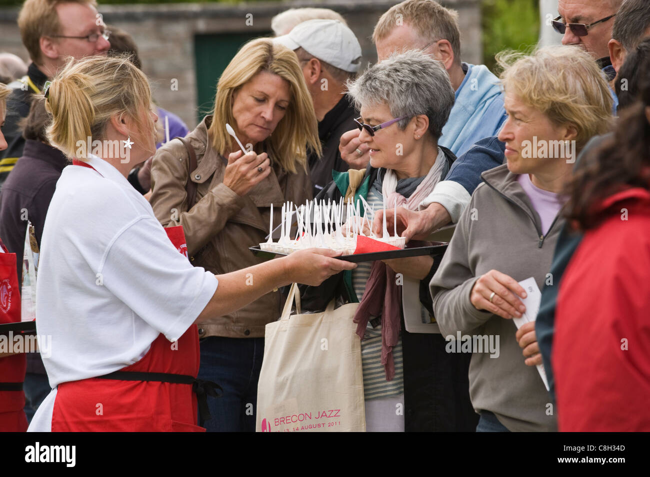 Queuing festivalgoers being offered samples of local food at