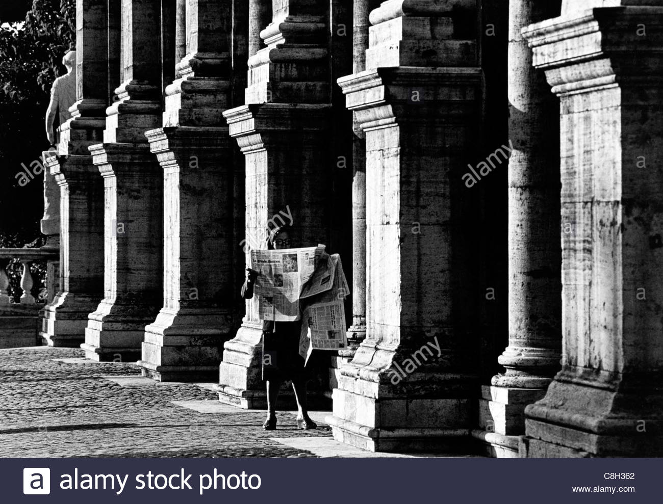 A woman reading a newspaper in front of the Palazzo Nuovo in Rome. - Stock Image