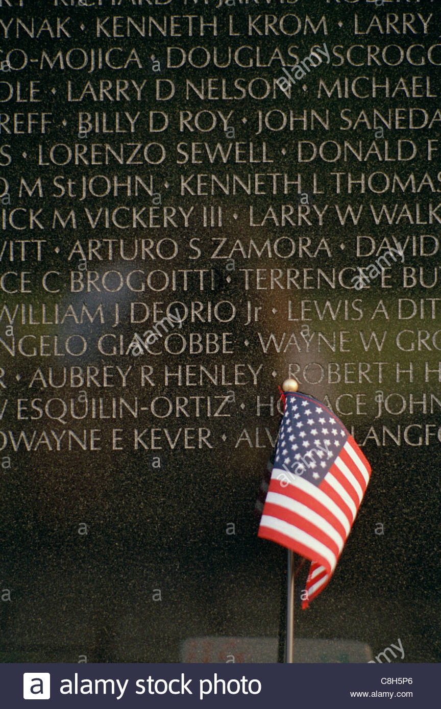 An American flag is left as a memento at the Vietnam Wall. - Stock Image