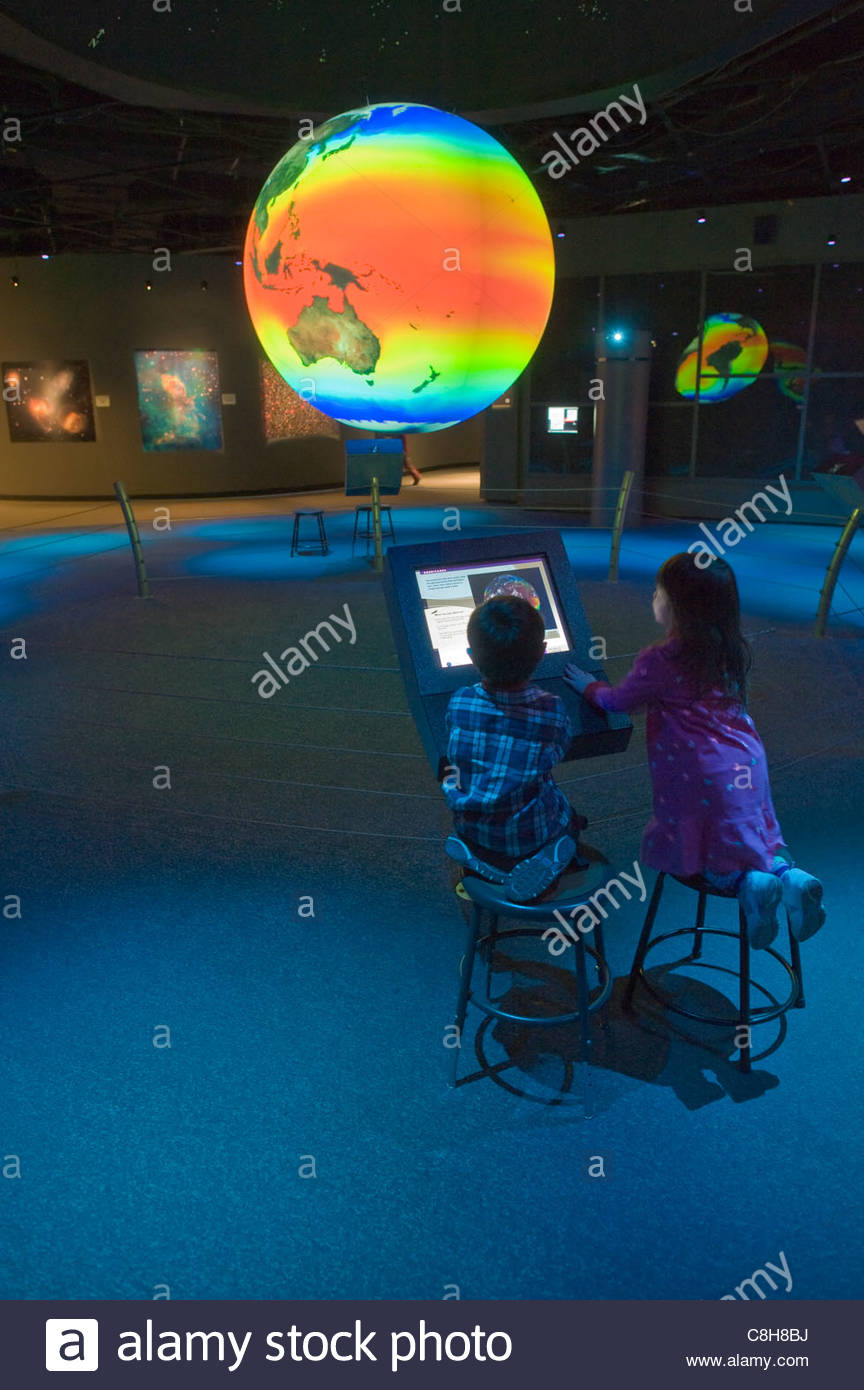 Children look at an astronomy exhibit at a museum. - Stock Image