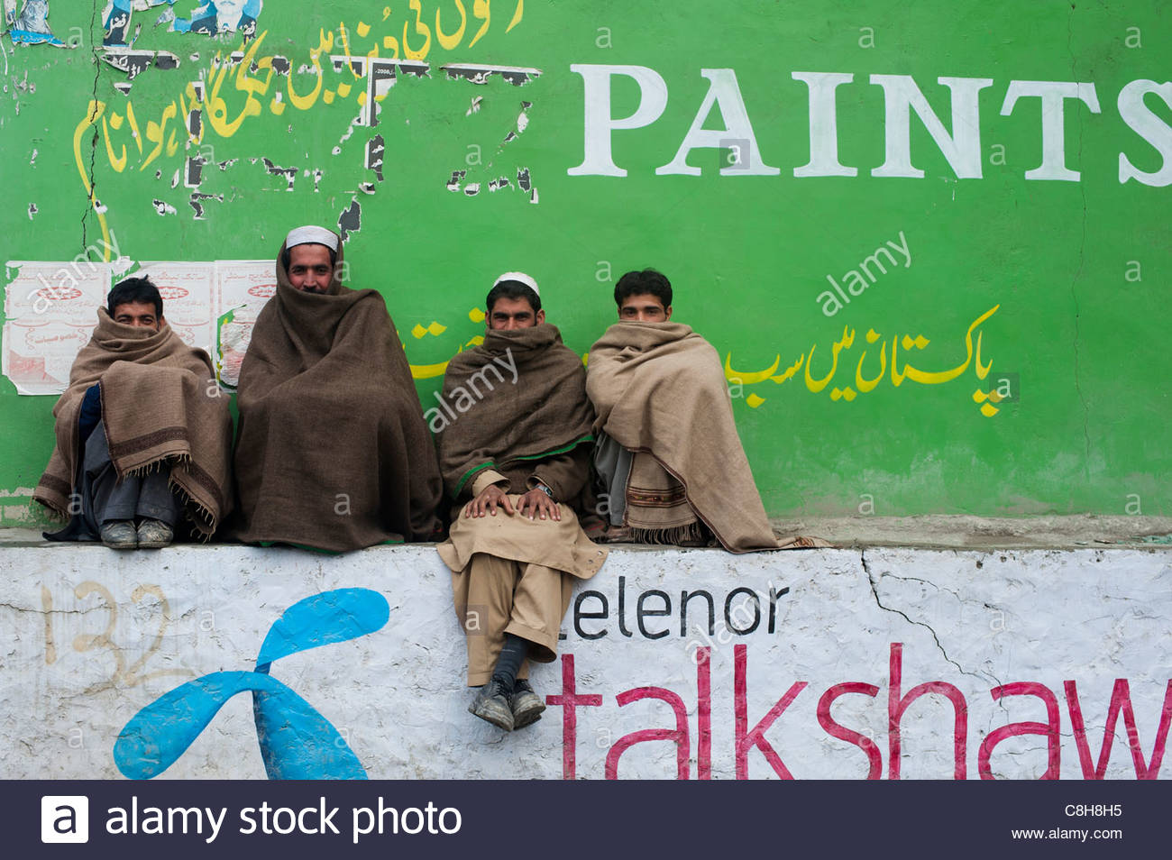 Men sit wrapped up to keep warm in Chitral. - Stock Image