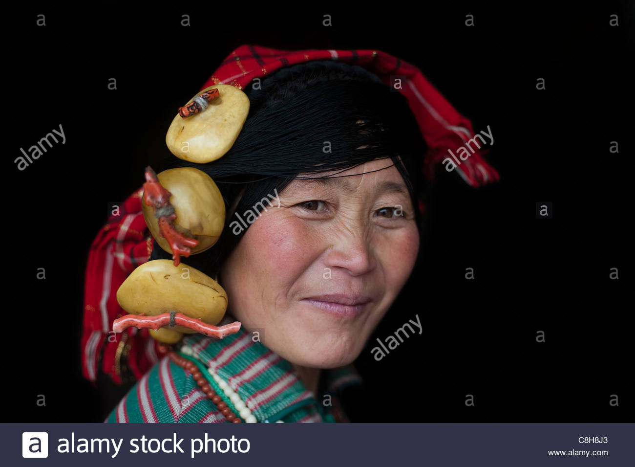 A Tibetan woman wearing traditional stone jewelry on her head. - Stock Image