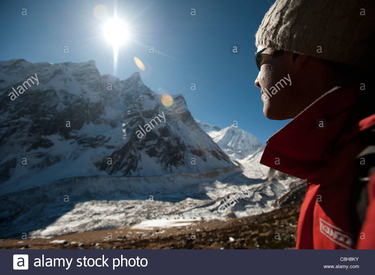 A trekker stops and admires the view of a glacier on the Manaslu trek. - Stock Image