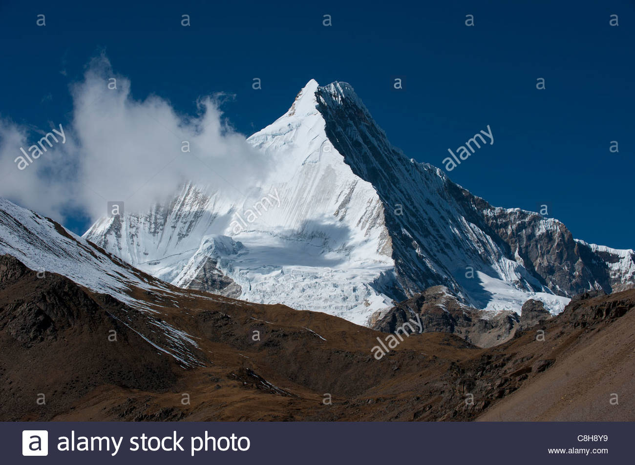 The white pyramid shape of Jichu Drake seen from the Nyile La pass - Stock Image