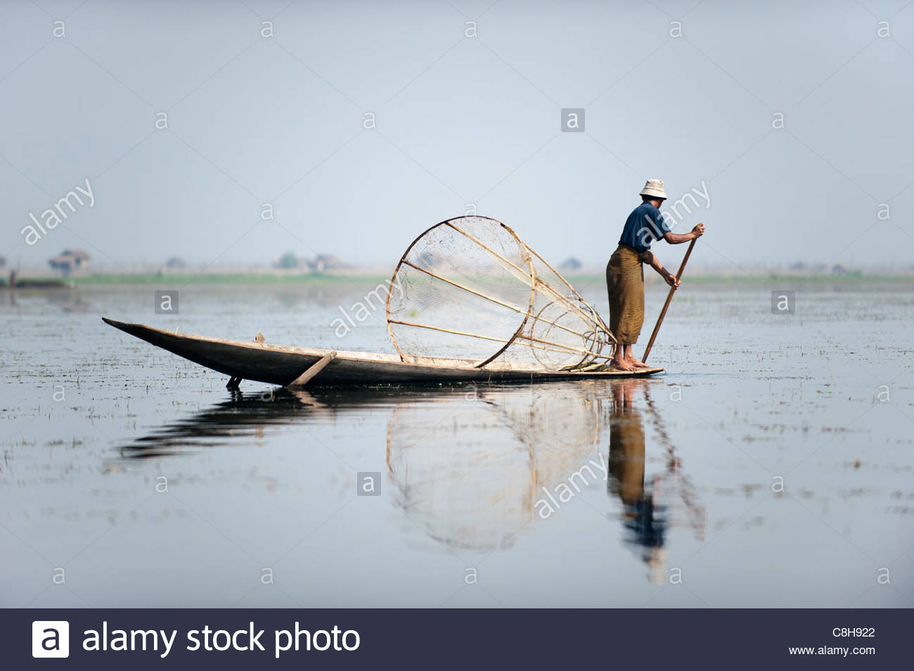 A basket fisherman scans Inle lake looking for fish in shallow water - Stock Image