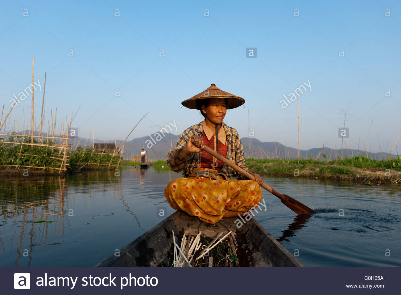 A woman paddles home through the floating gardens on Inle lake. - Stock Image