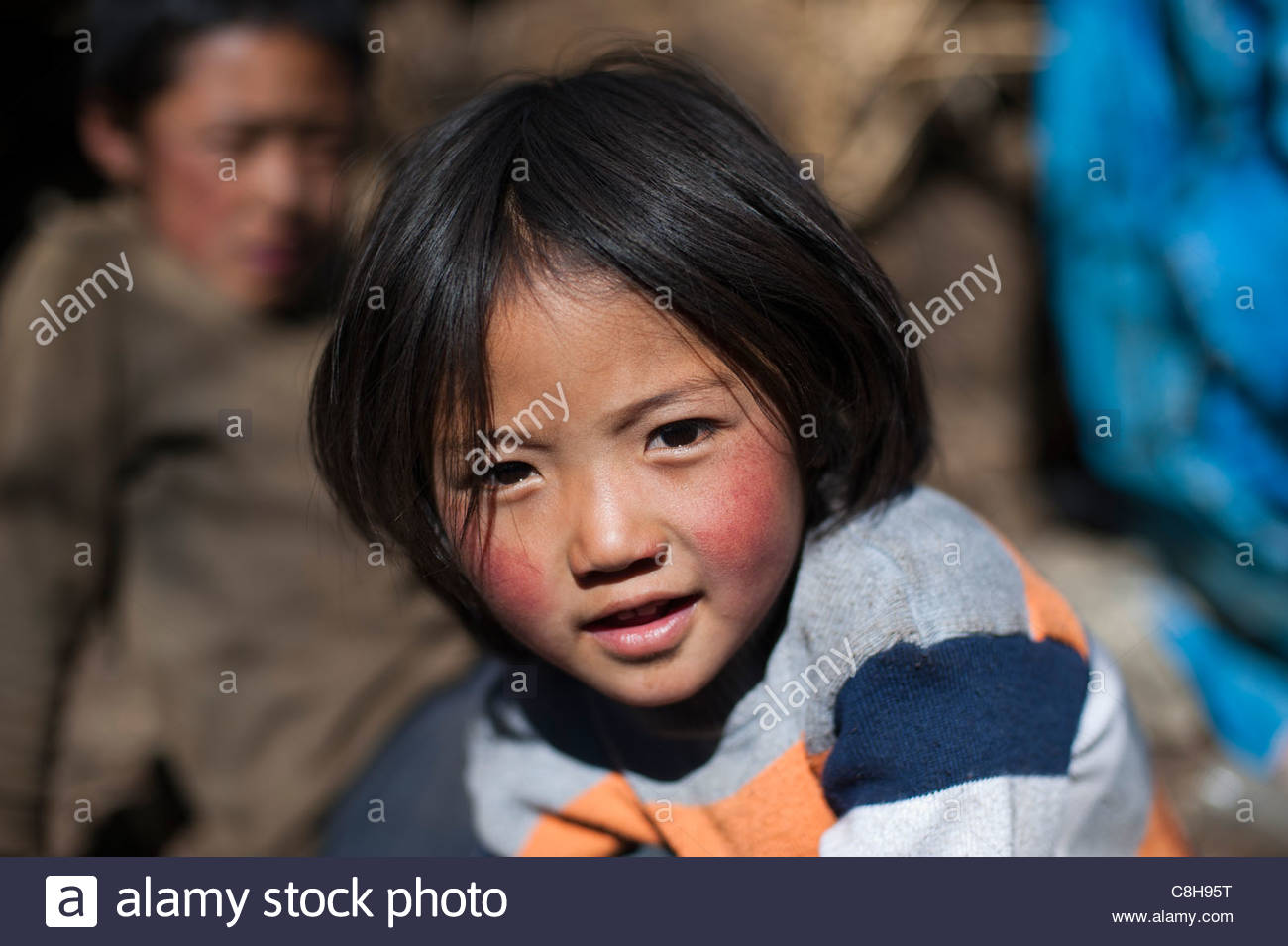 A little girl smile for the camera on the Laya-Gasa trek in Bhutan. - Stock Image