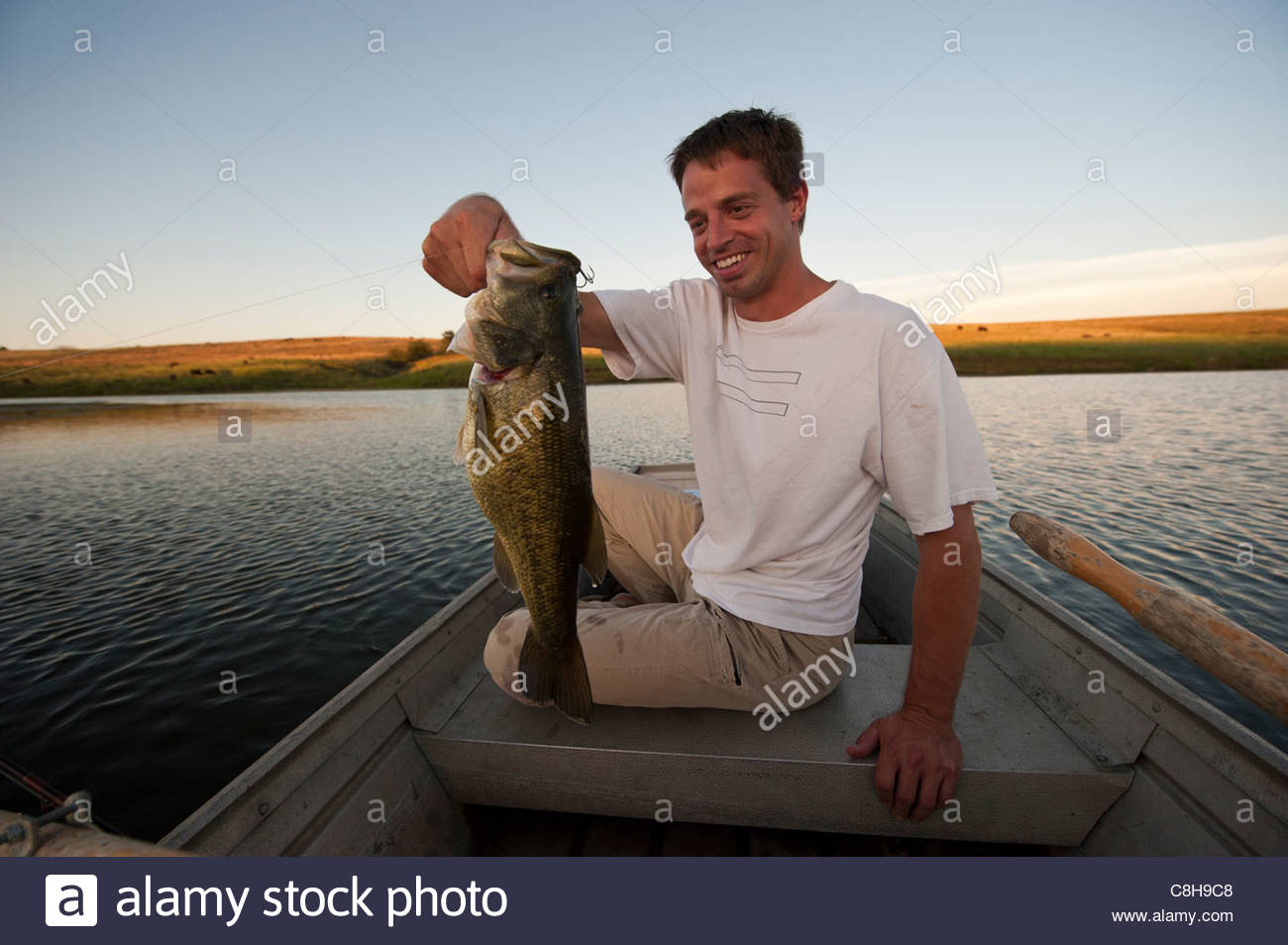 A man holds a fish he just caught at a small pond in Valparaiso, NE. - Stock Image