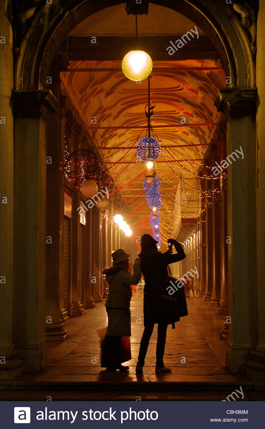 Tourists take pictures at night at the Piazza San Marcos. - Stock Image