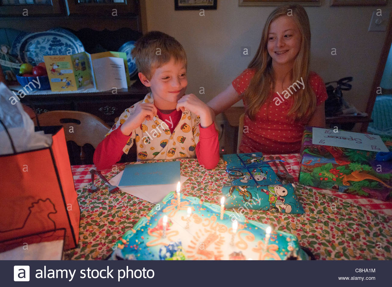 A young boy celebrates his 7th birthday with his older sister. - Stock Image