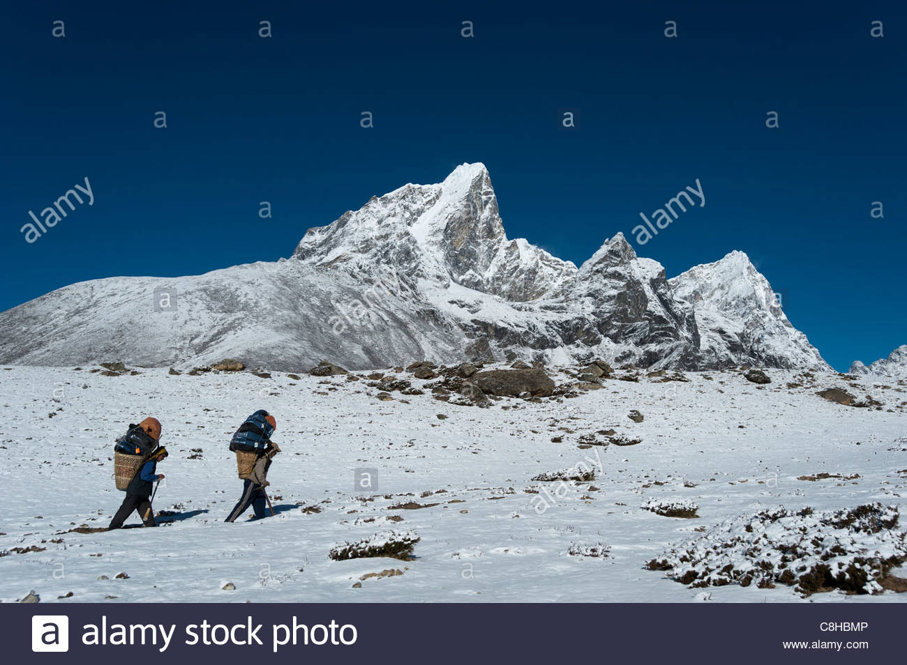 Porters make their way to base camp with views of Taboche behind - Stock Image