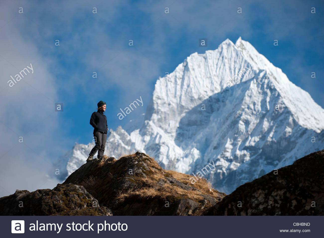 A trekker enjoys the views above Namche in the Everest region - Stock Image