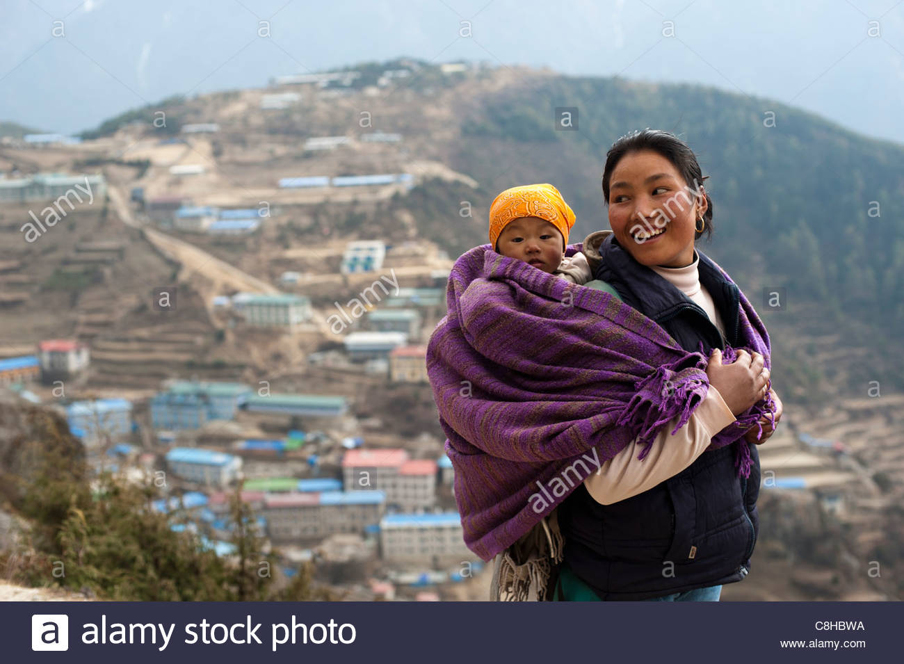 A woman carries her baby in a blanket with Namche visible behind. - Stock Image